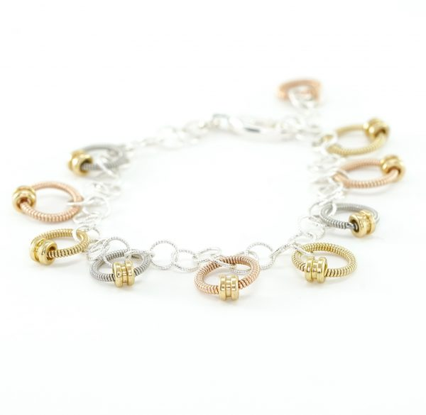 bracelet made of small rings of tri-metallic guitar string and ball ends laid out on a white background