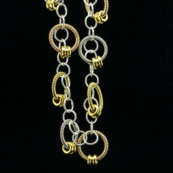 bracelet made of small rings of tri-metallic guitar string and ball ends hanging on a black background