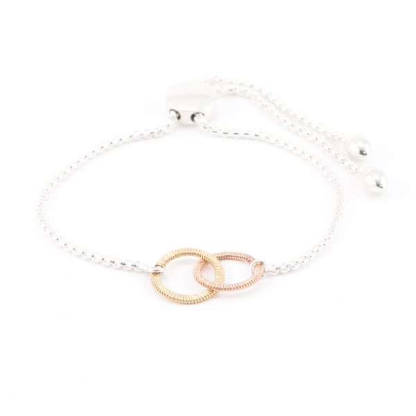 silver bracelet with interconnected circles of guitar string on white background