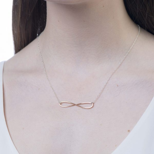 infinity shaped guitar string necklace with a silver chain hanging on a model