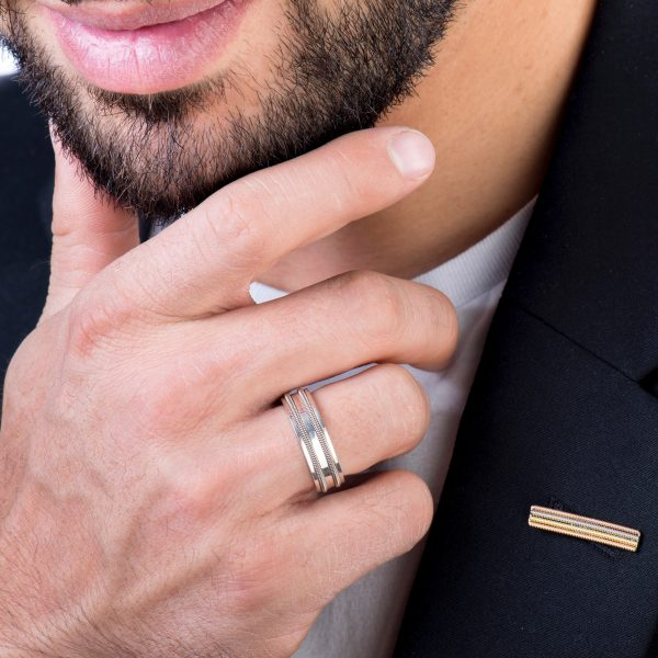 Lapel pin made from layers of recycled guitar string and guitar string ring on model, clowe-up