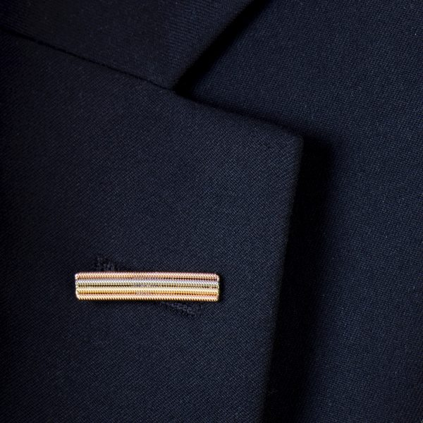 Lapel pin made from layers of recycled guitar string close-up on a suit jacket
