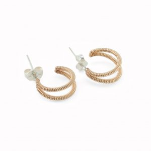small crescent shaped acoustic guitar string earrings on a white background