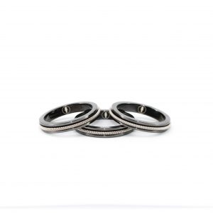 three black rings with inlaid electric guitar string on a white background