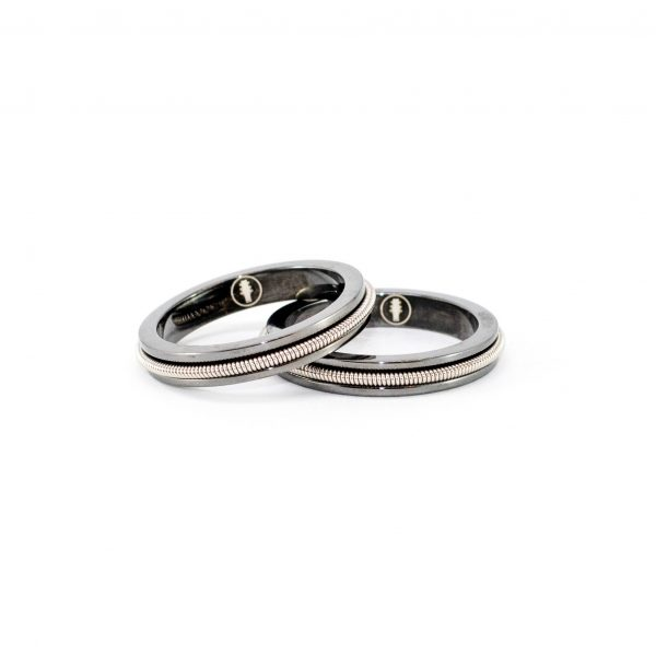 two black rings with inlaid electric guitar string on a white background