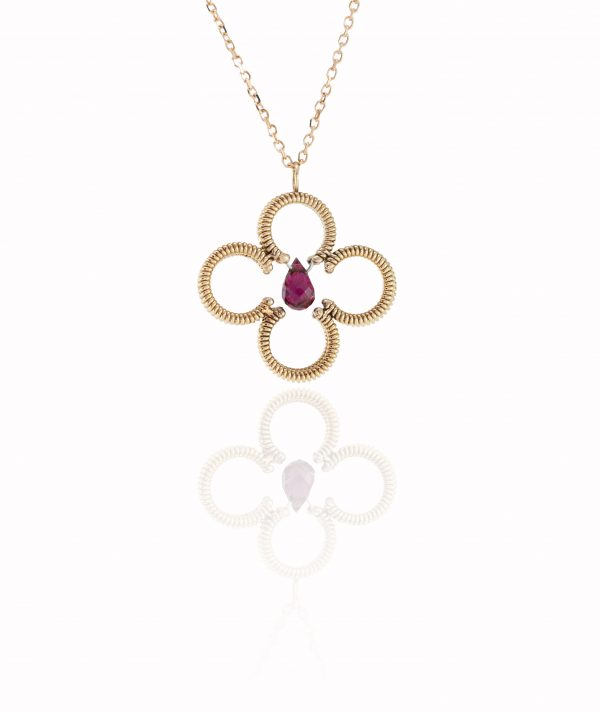 acoustic guitar string clover shaped pendant with a central red tourmaline gemstone with a rose gold chain on white background with reflection