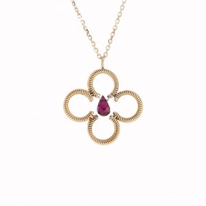 acoustic guitar string clover shaped pendant with a central red tourmaline gemstone with a rose gold chain on white background