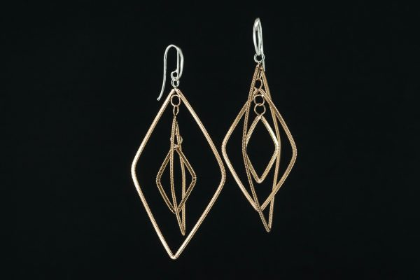 floating diamond-shaped dangling guitar string earrings with silver ear hooks on a black background
