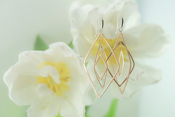 floating diamond-shaped dangling guitar string earrings with silver ear hooks and white tulips in the background