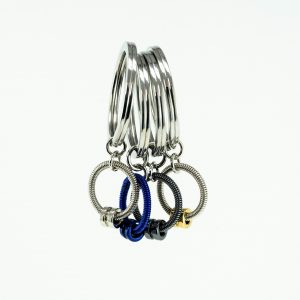 four bass guitar string key chains in silver, blue, and grey hanging with a white background